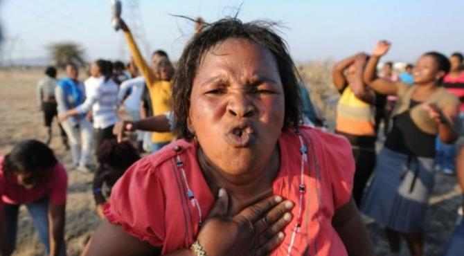 Women sing, dance and protest at the scene where 34 people died after police opened fire on striking mineworkers.  By  (AFP)