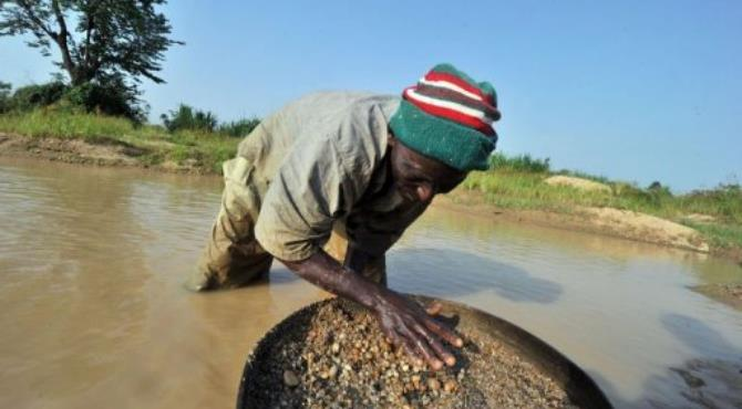 A diamond prospector filters earth from a river in April in Koidu.  By Issouf Sanogo (AFP/File)