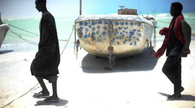 Two fishermen walk past a small fishing vessel on a beach in the coastal, central Somali town of Hobyo.  By Roberto Schmidt (AFP/File)
