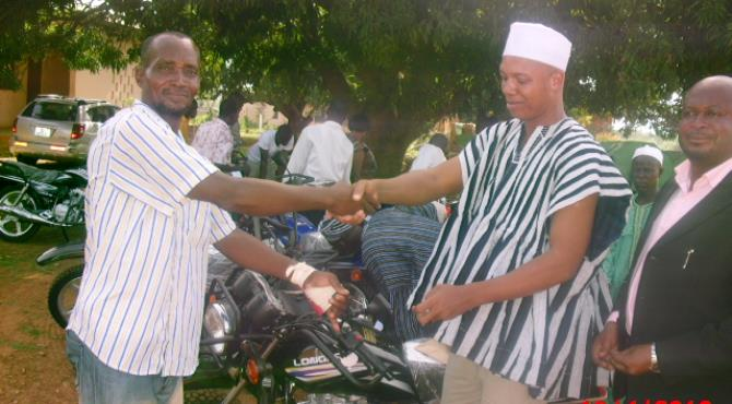 HON. ADAMS MUTAWAKILU(DCE) ON THE RIGHT PRESENTING THE KEYS TO ONE OF ASSEMBLYMEN.