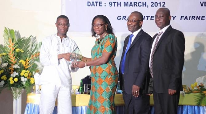 Adiki O. Ayitevie, Director, External Affairs & Communications at Newmont Ghana receiving the award from the Deputy Minister of Finance and Economic Planning, Fifi Kwetey.