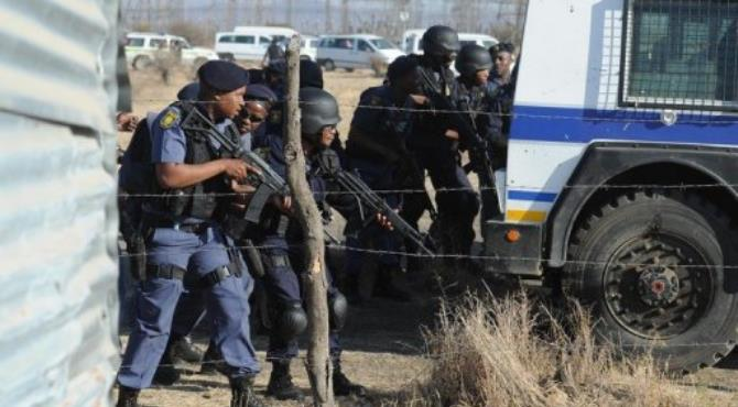 Police face the miners during the clash at the Marikana mine on Thursday.  By Stringer (AFP/File)