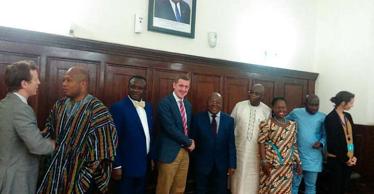 Ian Walker (middle) in a handshake with Prof Mike Oquaye