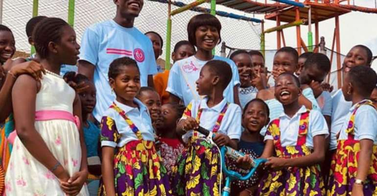 Bright Ofori and Rebecca Kwabi engaging with some children at the event