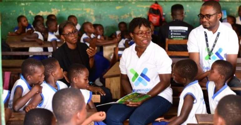 Madam Angela okai reading to the pupils