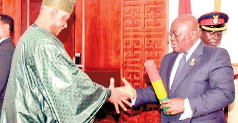 President Akufo-Addo presenting the instrument of office to Ahmed Ramadan at the Flagstaff House on Accra Wednesday