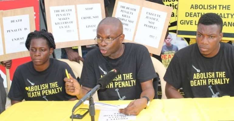 Mr Samuel Komla Agbotsey (middle), Campaigns and Fundraising Co-ordinator for Amnesty International, Ghana, addressing the public on the impact of the death penalty on children. With him are Paul Gozo (right) and Gloria Emeka, both members of AI Ghana . Picture: Patrick Dickson