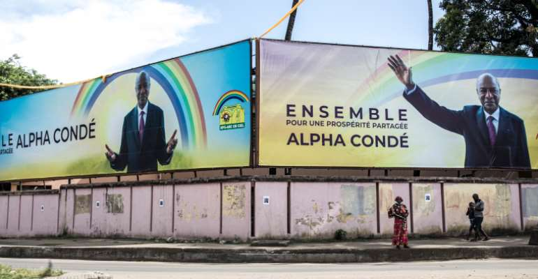 People walk under a campaign billboard for President Alpha Conde in Conakry, Guinea, on October 12, 2020. CPJ recently joined a letter calling on the Guinean government to maintain internet access throughout the presidential election. (AFP/John Wessels)