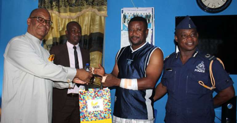 Mr. Ray Anselm Sowah presents a package to the Kasoa police