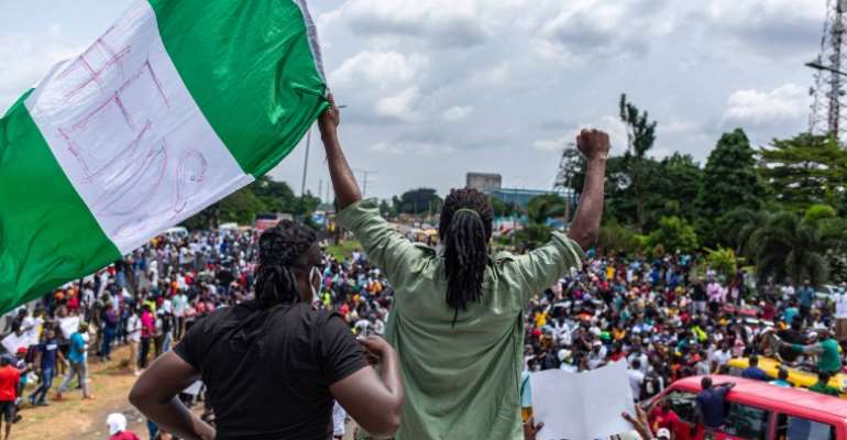 A youth is seen waving the Nigerian flag during protests against police brutality in Lagos on October 13, 2020. CPJ called for journalists' safety to be protected amid the protests. (AFP/Benson Ibeabuchi)