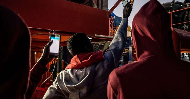 Migrants try to get network on their phones  in Algeciras, Spain.  - Source: Photo by Ignacio Marin/Anadolu Agency/Getty Images