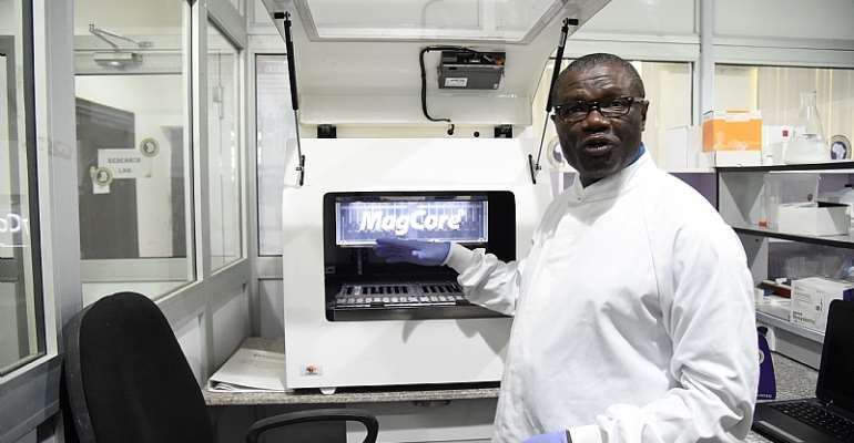 Professor Christian Happi, director of the African Centre of Excellence for Genomics of Infectious Diseases, displays one of the most advanced automated acid extractors being used in the laboratory.   - Source: Pius Utomi Ekpei/AFP via Getty Images