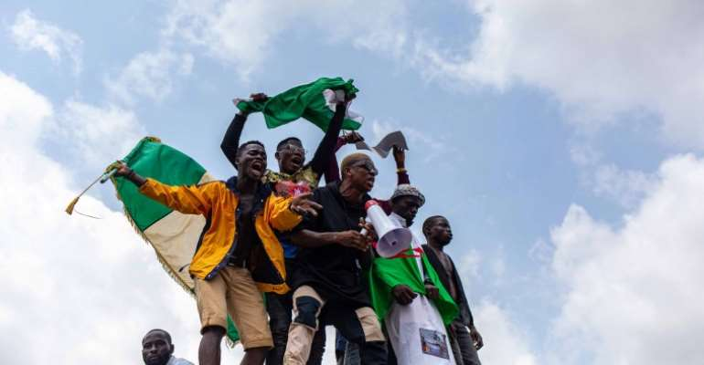 Nigerian youths seen waving the Nigerian national flag in front of a crowd in support of the ongoing protest against the unjust brutality of The Nigerian Police Force Unit named Special Anti-Robbery Squad (SARS) in Lagos on October 13, 2020. Journalists have been attacked by law enforcement and unidentified assailants during the protests. (AFP/Benson Ibeabuchi)