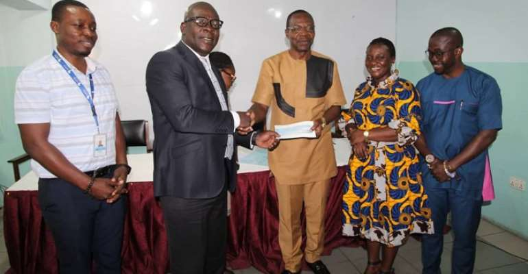 Mr Frank Ebo Brown (2nd left) presenting a cheque to Dr. Affail Monney (3rd right)