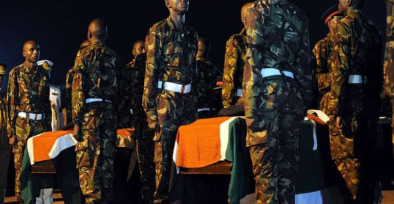 Kenyan soldiers stand over caskets bearing the remains of their fallen comrades during prayers in 2016. - Source: Tony Karumba/AFP via Getty Images