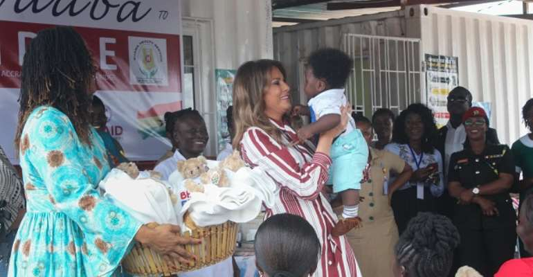 Mrs. Melania Trump holding a baby at the child welfare clinic during her visit