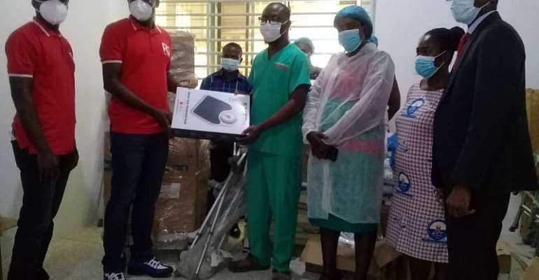 Mr. Amankwaah (Project Manager of Project Ghana) presenting the items to Dr. Randolph Baah Adu, Medical Superintendent of the Hospital.  Extreme right is the Board Chairman of the Hospital Pastor  Asamoah Kwarteng