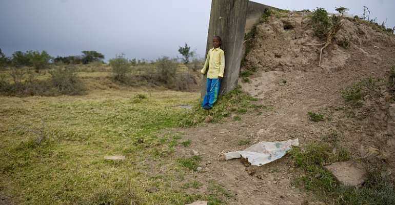 Young Sandi Sile on an abandoned structure in  Makhanda, South Africa, in 2013. Questions remain about how the new law will treat abandoned land.  - Source: Getty Images