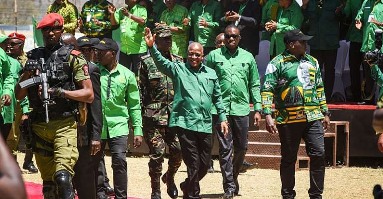 John Magufuli (centre) waves as he arrives to give a speech at a campaign rally in August 2020.  - Source: