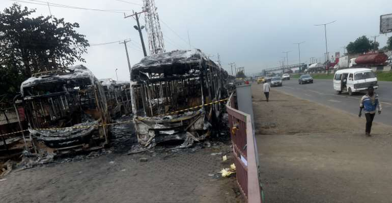 People in Lagos on October 26, 2020, walk past buses burnt during a protest against police brutality. Nigerian President Muhammadu Buhari on October 25 appealed for