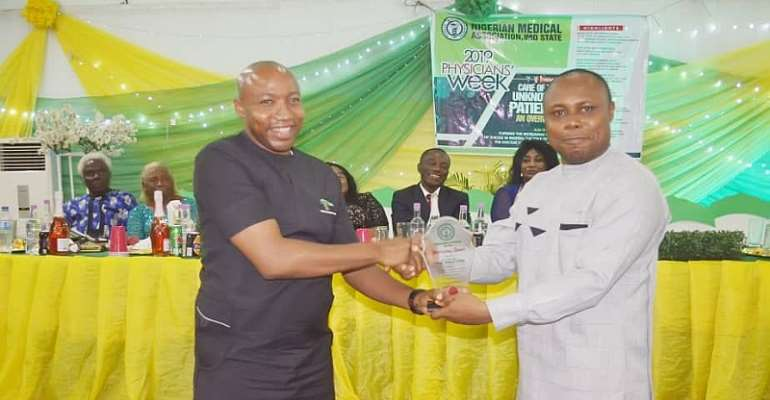 SSA, Media and Communications to the Deputy Governor, Dr. Walter Duru(L) receiving NMA Meritorious Service Award from NMA Chairman onbehalf of the Deputy Governor, Gerald Irona