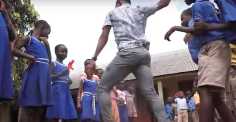 Percy Sackey with his pupils in the school compound, dancing