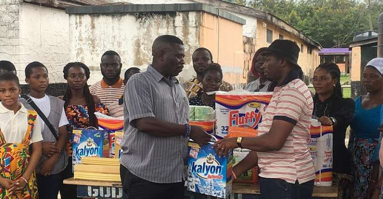 Mr. Prosper Agbenu, Chairman of the ARS Youth Ministry (right) presenting the items to the Prisons Officer