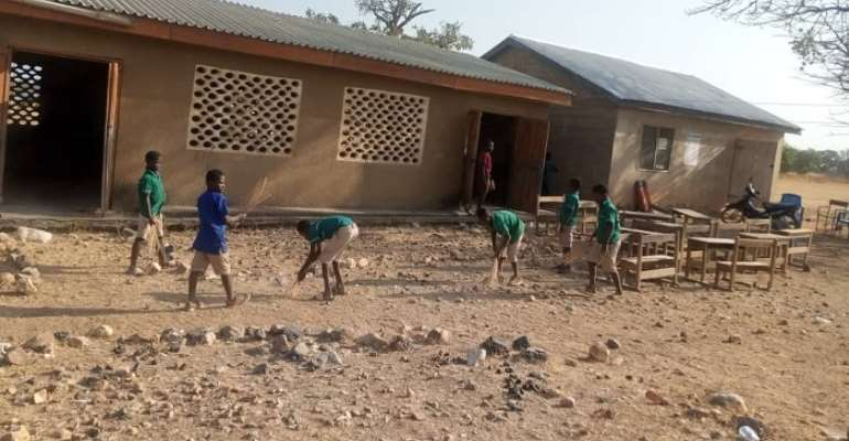 School children cleaning their school on first day of reopening
