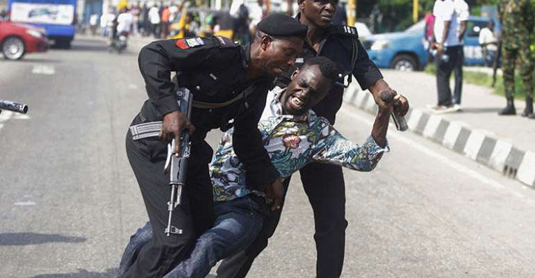 Police officers detain Sahara Reporters journalist Victor Ogungbenro during a protest in Lagos, Nigeria, on August 5, 2019. Staff at the online newspaper report sustained harassment targeting them and their website. (AP/Sunday Alamba)