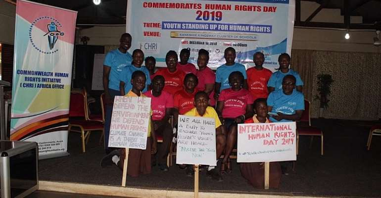 Students from Kaneshie Kingsway Cluster of Schools display placards and read the Statement from the UN High Commissioner for Human Rights