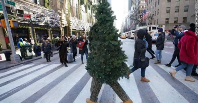 A man dressed up as a Christmas tree is walking around New York City