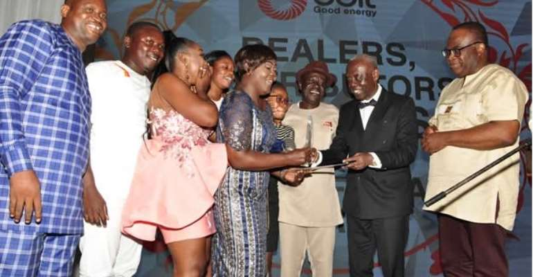 Dealer of Sebrepor GOIL service station, Georgina Gyabeng receiving the best dealer award from Board Chairman, Kwamena Bartels, whilst Kwame Osei Prempeh (3rd R), Mr. Kwaku Agyeman Duah (extreme R) and workers of Sebrepor service station look on.
