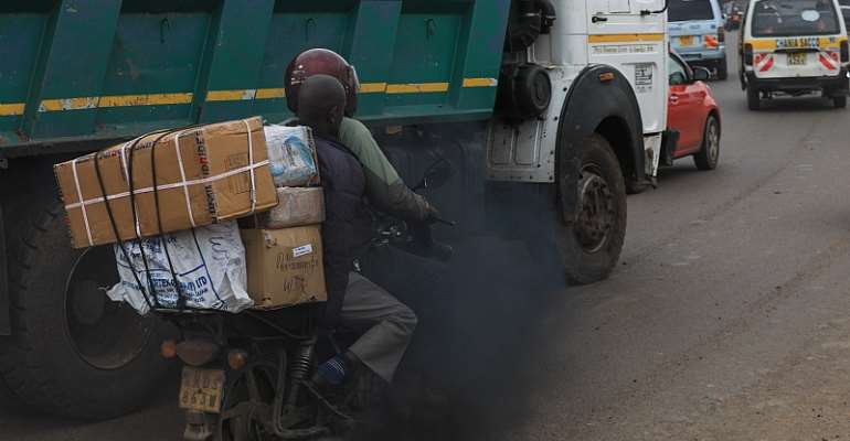 Black exhaust fumes from lorry envelope a motorcyclist and his passenger on a busy road in the Kenyan capital, Nairobi.  - Source: EPA-EFE/Daniel Irungu