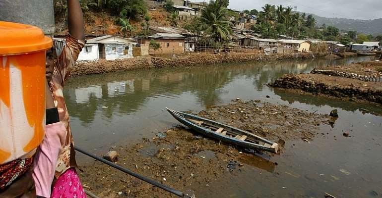 Girls carry drinking water across a bridge in Freetown, Sierra Leone. - Source: EPA/Nic Bothma
