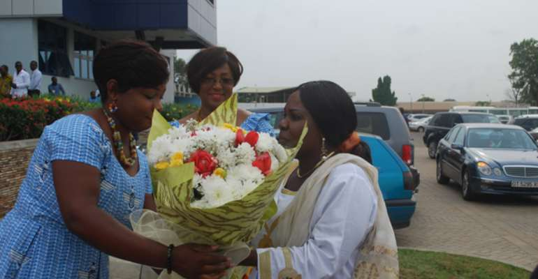 Cecilia Dapaah receiving a bouquet of flowers on arrival