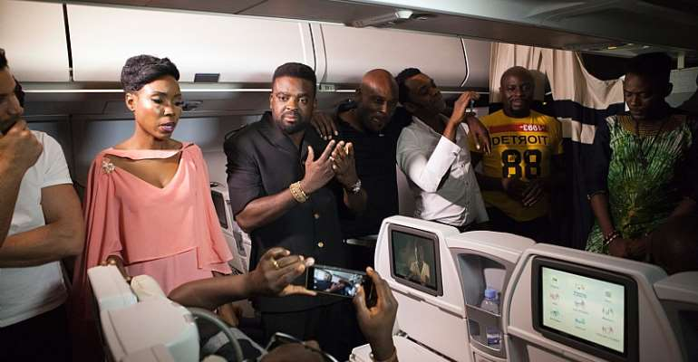 Nigerian director Kunle Afolayan speaks with passengers aboard a flight during the premiere of his film, The CEO. - Source: Florian Placheur/AFP/Getty