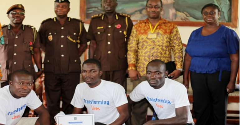 Three participants (inmates) in a pose with some of the dignitaries present