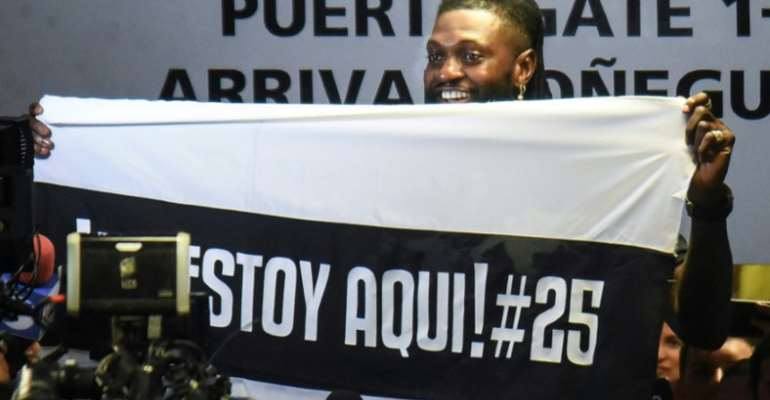 Togo forward Emmanuel Adebayor holds up a message to his new fans at Paraguay champions Olimpia on his arrival in Asuncion