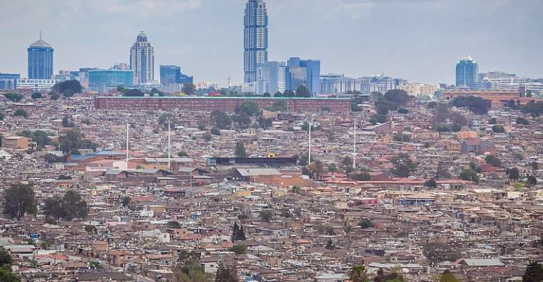South Africa's Alexandra township in the foreground, where the  majority live in squalor, and Sandton in the background, representing the most privileged  - Source: Shutterstock
