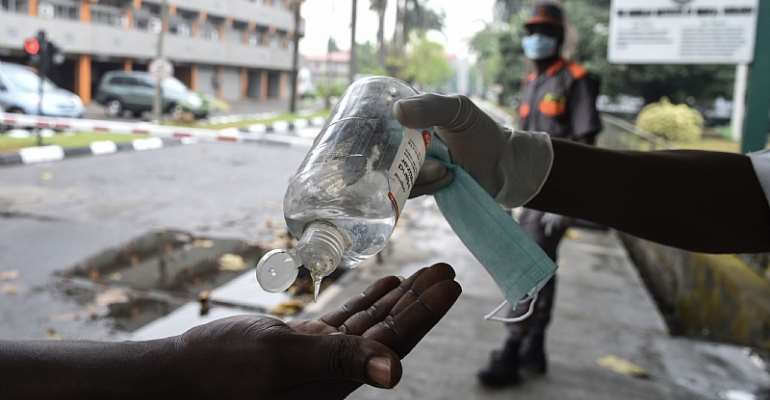 A visitor sanitises hands before entering a state hospital at Yaba, Lagos. Hospitals like this are likely to suffer power cuts as lock down force Nigerians to stay at home and consume more power.   - Source: Photo by Pius Utomi Ekpei/AFP via Getty Images