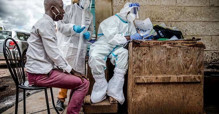 Health workers collect data from a man before taking samples during Kenya's COVID-19 mass testing exercise. - Source: Photo by LUIS TATO/AFP via Getty Images