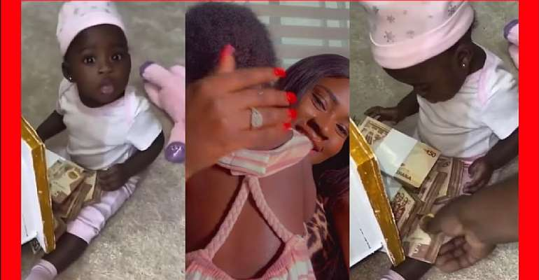 Fella Makafui splashes bundles of Ghc50 notes on her daughter, baby Island Frimpong [Video]