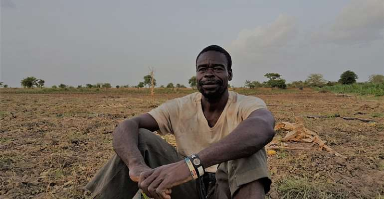 A Ghanaian vegetable farmer sits on his land - Source: