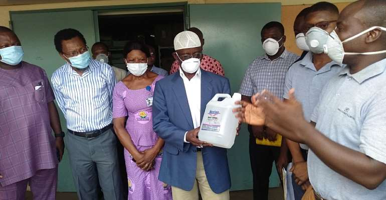 Dr Mumuni (in white hat) holding a gallon of hand sanitiser