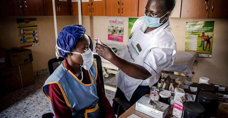 A doctor measures a worker's temperature in Kitui, Kenya. With technology, AI and human resources, Africa's health systems can take on COVID-19. - Source: Photo by LUIS TATO/AFP via Getty Images