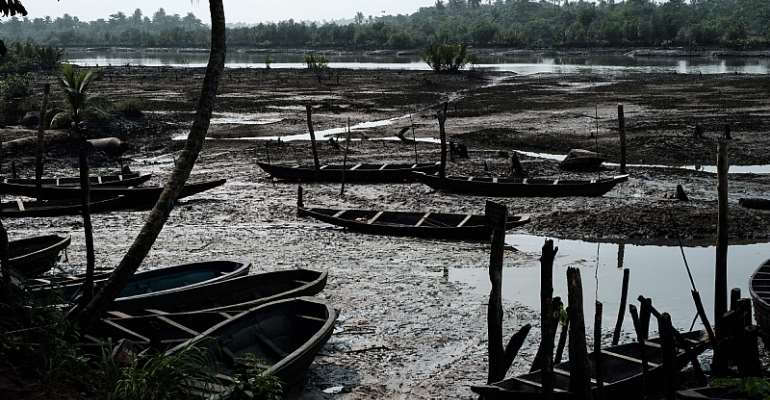 Oil smeared fishboats on oily mud in the river during low tide at K-Dere, near Bodo in the Niger Delta region  - Source: