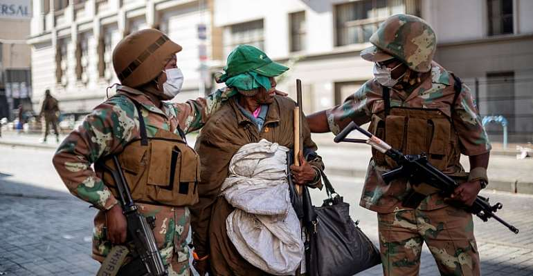 Soldiers escort a homeless woman to a gathering point in the Johannesburg CBD during the nationwide Covid-19 lockdown.  - Source: Michele Spatari/AFP-GettyImages