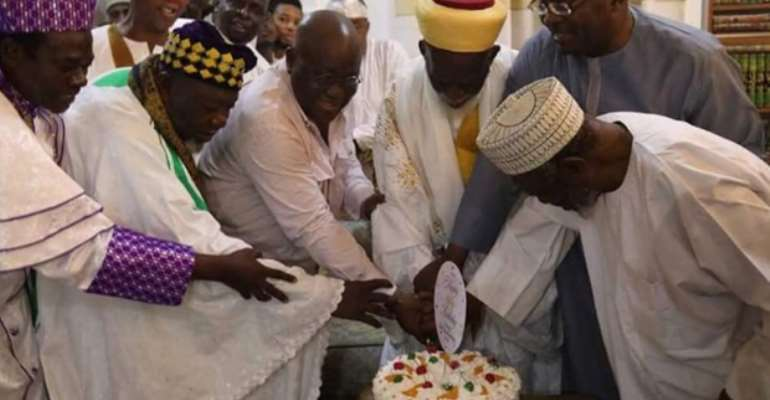 The cleric being assisted to cut the birthday cake