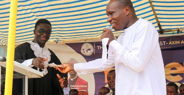 Ellembelle DCE, Kwasi Bonzoh presenting cheque to the District Head Pastor of Esiama The Church of Pentecost