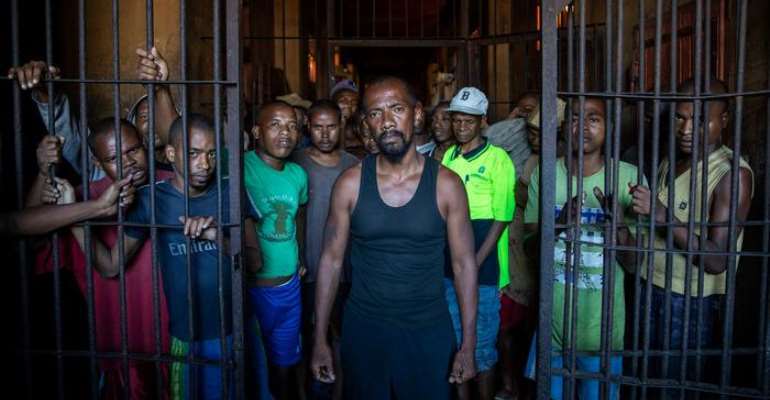A group of pre-trial detainees in Madagascar stand behind half-opened prison bars